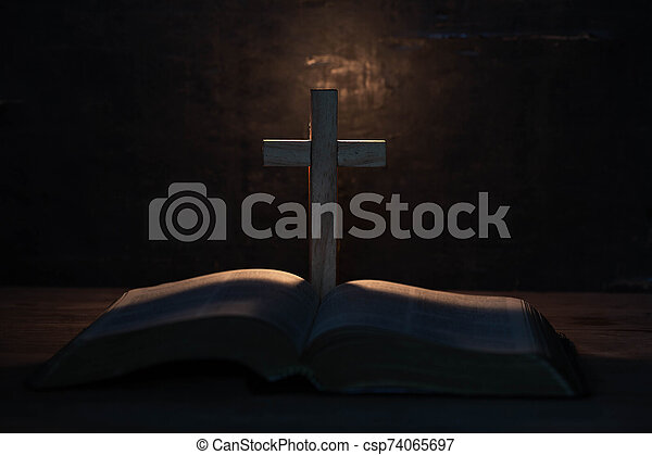 cross and holy Bible on wooden table - csp74065697
