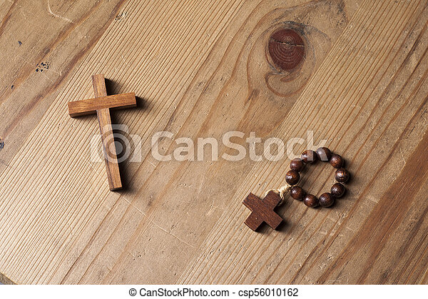 Cross and rosary over wood table with window light - csp56010162