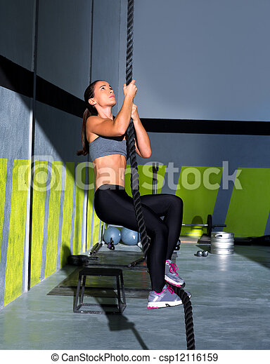 cross fit rope climb exercise in fitness gym workout