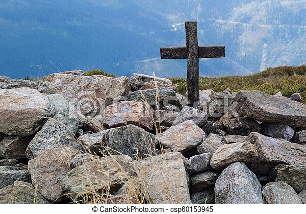 Cross on the top of a mountain in central europe. A wooden sign of Christianity lined with stones. - csp60153945