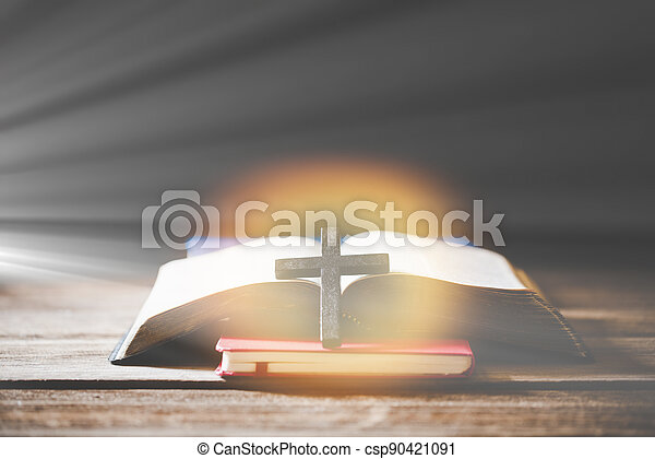 Cross with Bible on a old oak wooden table. - csp90421091