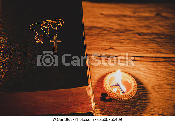 Cross with Holy Bible and candle on a old oak wooden table. - csp68755469