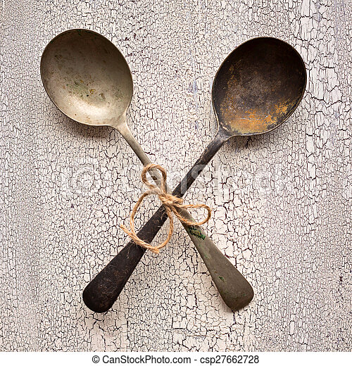Crossed Old vintage spoons on white wooden background, top view - csp27662728