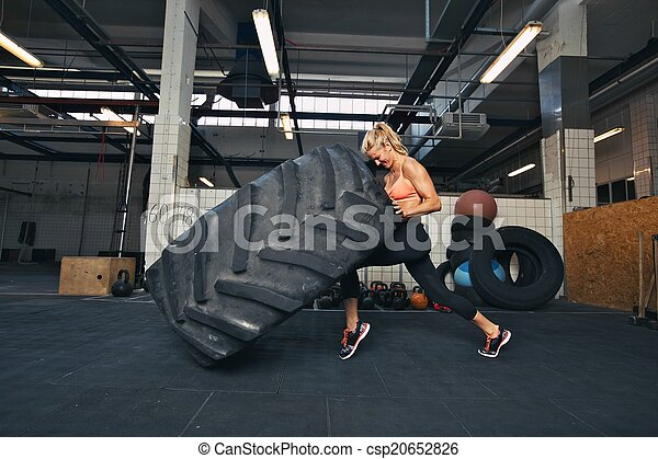 Crossfit woman flipping a huge tire at gym - csp20652826