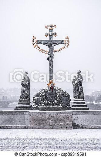 Crucifix statue on Charles Bridge in Prague - csp89319591