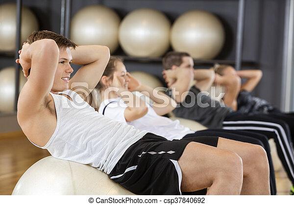 Hombre haciendo abdominales con amigos en la pelota en el gimnasio - csp37840692