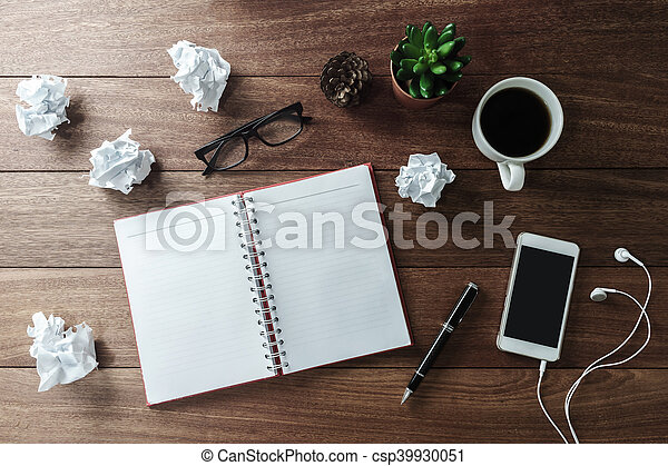 Crumpled paper balls with cup of coffee and notebook on wooden desk - csp39930051