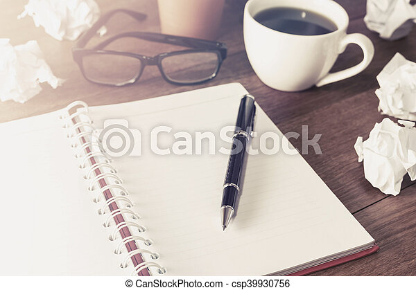 Crumpled paper balls with cup of coffee and notebook on wooden desk - csp39930756
