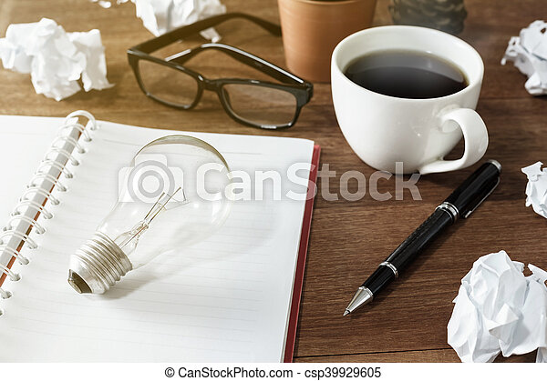 Crumpled paper balls with cup of coffee and notebook on wooden desk - csp39929605