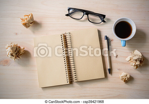 Crumpled paper balls with eye glasses, pen and notebook with cup of coffee - csp39421968
