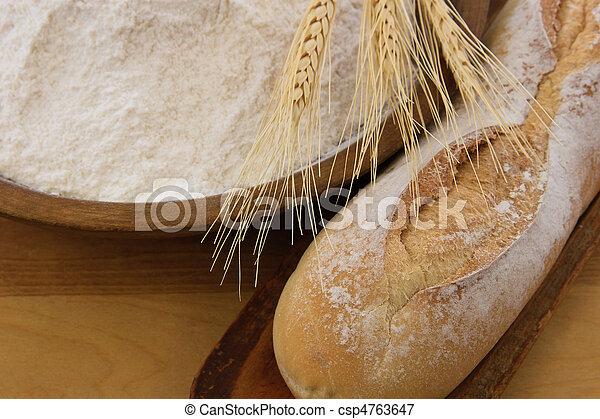 Crusty baguette bread with wooden bowl full of flour - csp4763647