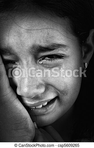 Crying girl, tears on cheeks, low light key, added grain, black and white - csp5609265