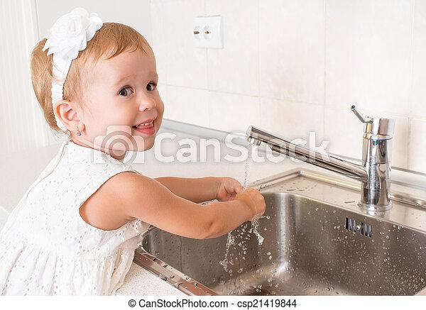 La niña se lava las manos en el baño - csp21419844