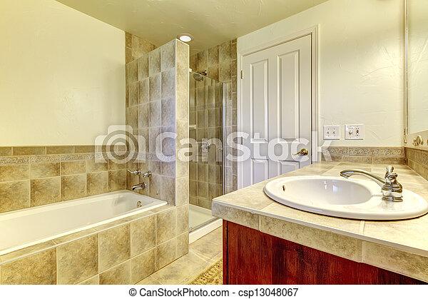 Baño con bañera, ducha pequeña y armarios de madera.