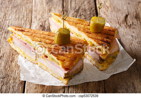 Cuban sandwich with ham, mustard, cheese, pickled and pork close-up. horizontal - csp53072539