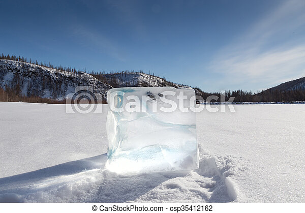 cube of ice on the snow - csp35412162