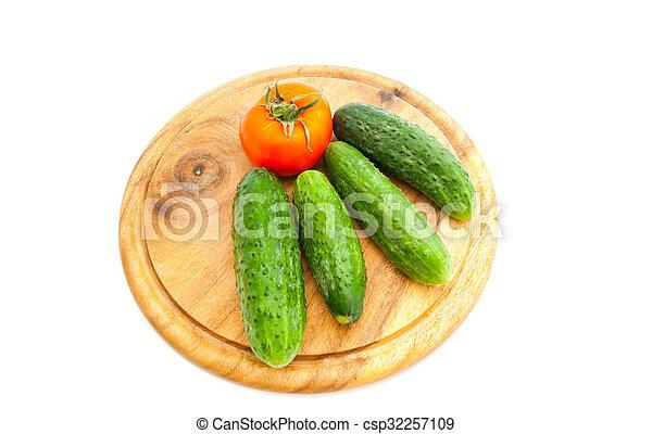 cucumbers and tomato on cutting board - csp32257109