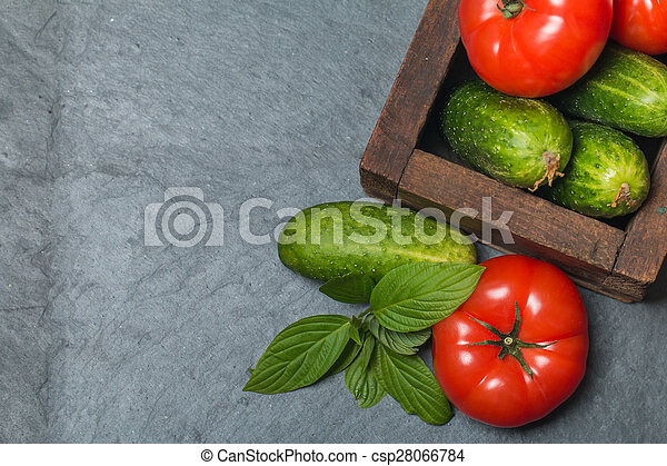 Cucumbers and Tomatoes in wooden box - csp28066784