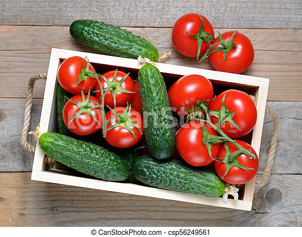 Cucumbers and tomatoes in wooden box top view - csp56249561
