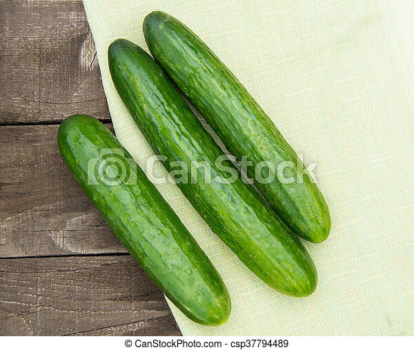 Cucumbers are lying on an old wooden background with napkin - csp37794489