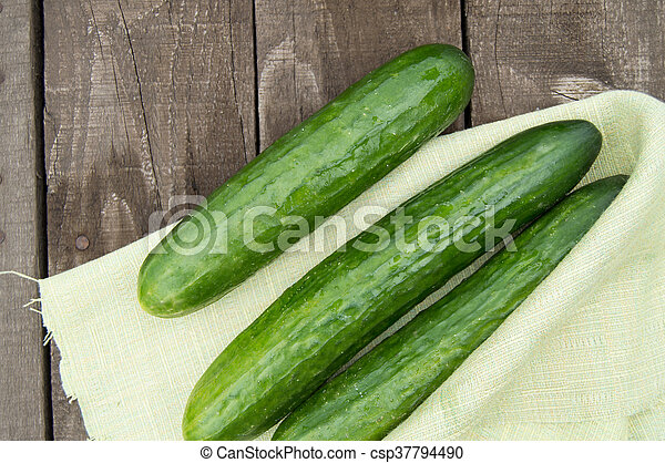 Cucumbers are lying on an old wooden background with napkin - csp37794490