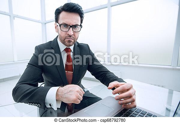 Un hombre de negocios serio revisando cuentas mientras está sentado en su escritorio - csp68792780