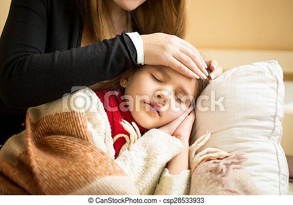 El primer plano de la madre cariñosa sosteniendo la cabeza en la frente de la hija enferma - csp28533933