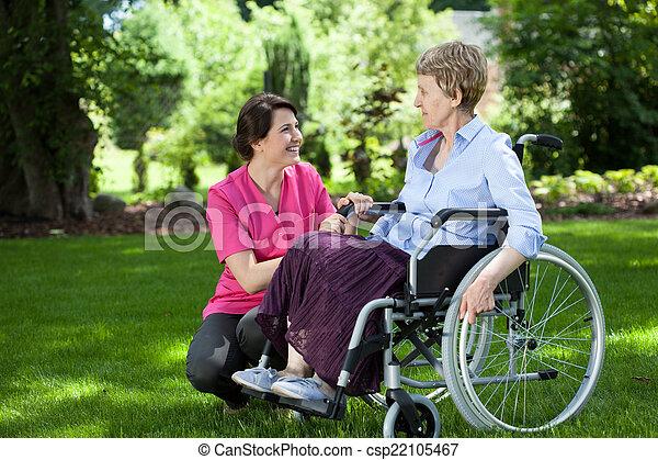 Una anciana en silla de ruedas con cuidadora - csp22105467