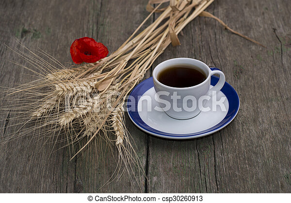cup of black coffee, bunch of wheaten ears and flower of poppy - csp30260913