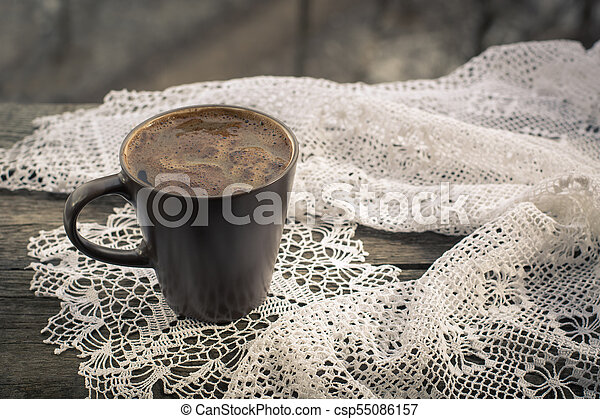 Cup of black coffee in front of the window and lace on wooden background. - csp55086157