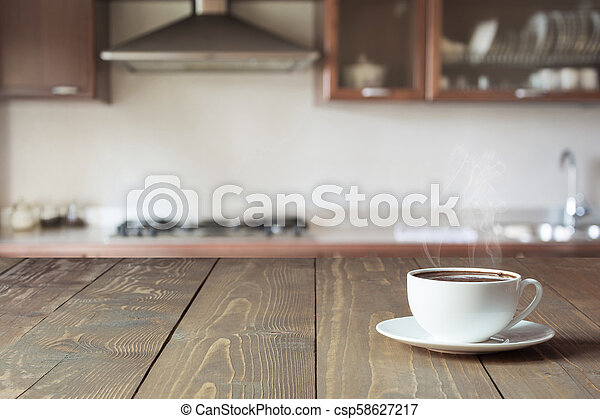 Cup of black coffee on wooden tabletop in blurred modern kitchen. Close up. Indoor. - csp58627217