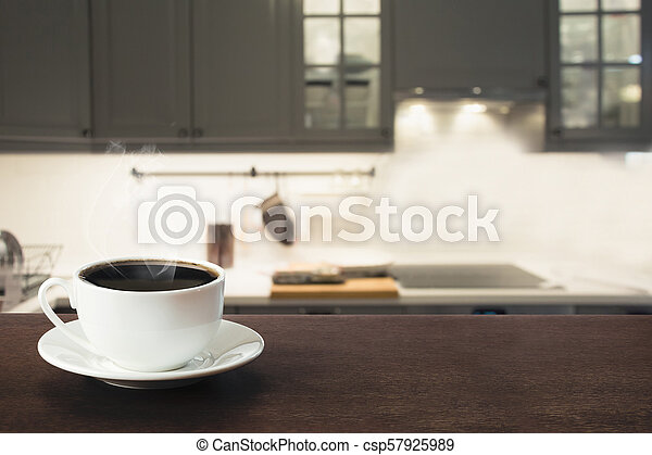 Cup of black coffee on wooden tabletop in blurred modern kitchen. Close up. Indoor. - csp57925989