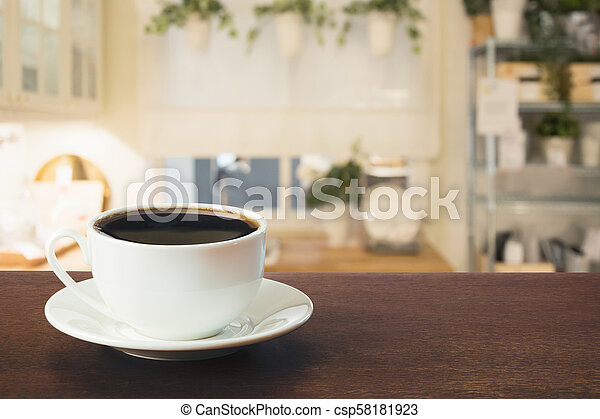 Cup of black coffee on wooden tabletop in blurred modern kitchen or cafe. Close up. Indoor. - csp58181923
