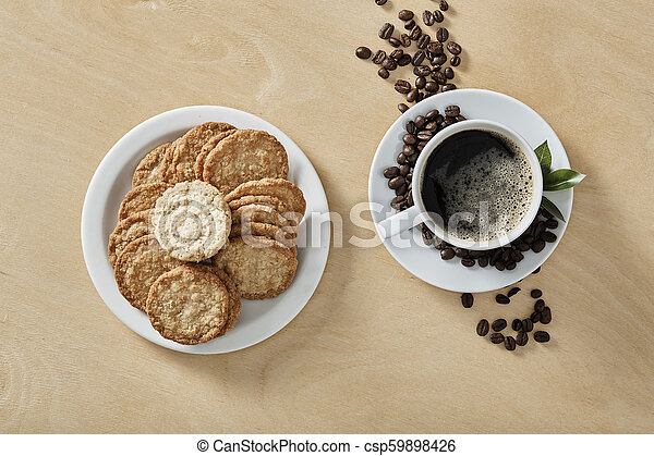 Cup of black coffee whit cookies on white plate and wooden background. Top view. - csp59898426