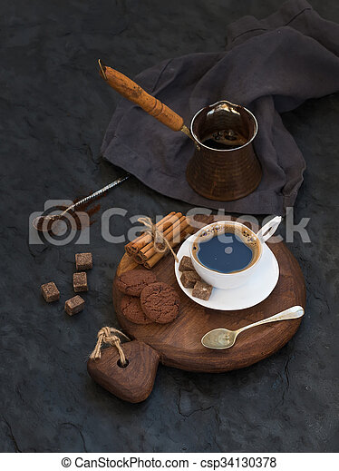 Cup of black coffee with chocolate biscuits, cinnamon sticks and cane sugar cubes on rustic wooden board over dark stone backdrop. - csp34130378