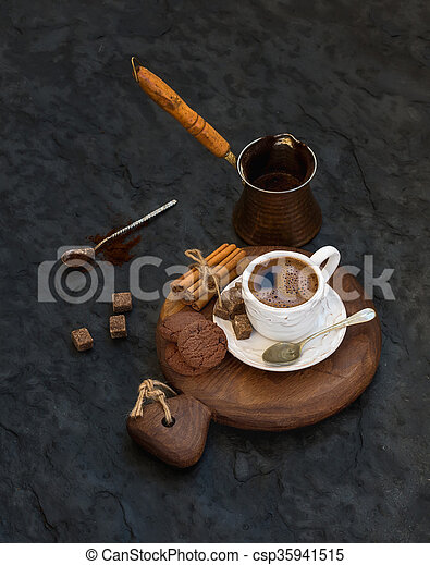 Cup of black coffee with chocolate biscuits, cinnamon sticks and cane sugar cubes on rustic wooden board over dark stone backdrop. - csp35941515