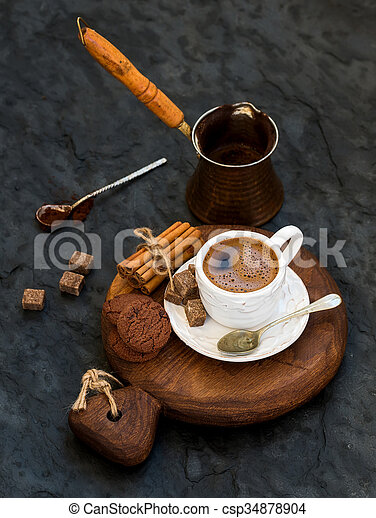 Cup of black coffee with chocolate biscuits, cinnamon sticks and cane sugar cubes on rustic wooden board over dark stone backdrop. - csp34878904