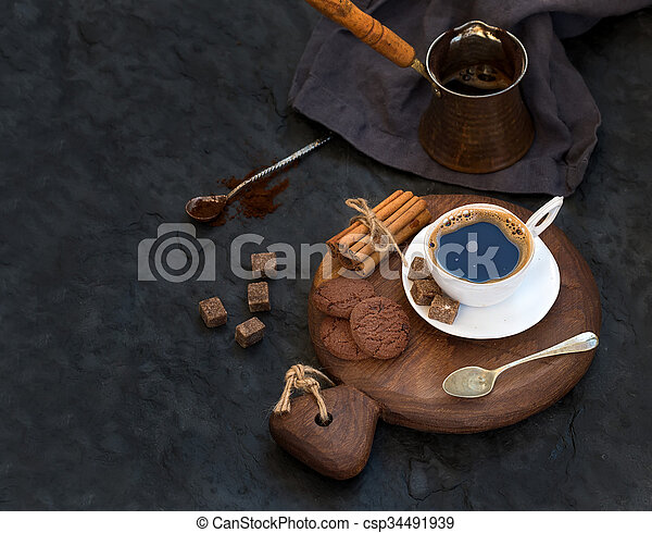 Cup of black coffee with chocolate biscuits, cinnamon sticks and cane sugar cubes on rustic wooden board over dark stone backdrop. - csp34491939
