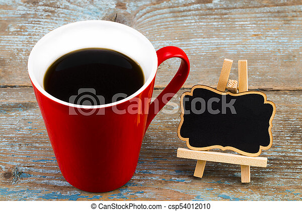 Cup of coffee and a blackboard with empty space for a text on wooden background - csp54012010