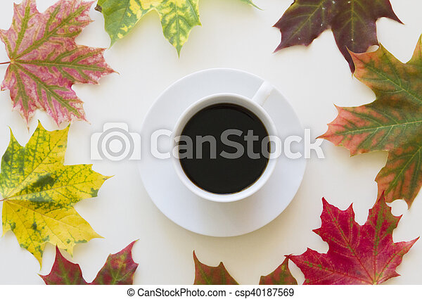 Cup of coffee, framed with autumn leaves on white background. Flat lay. Top view - csp40187569