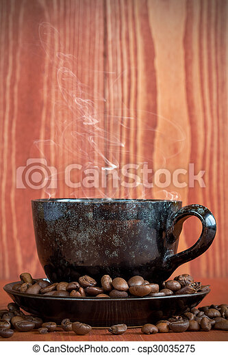 Cup of coffee on a brown background with coffee beans - csp30035275