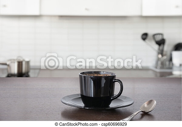 Cup of coffee on wooden board. Blurred kitchen as background. - csp60696929