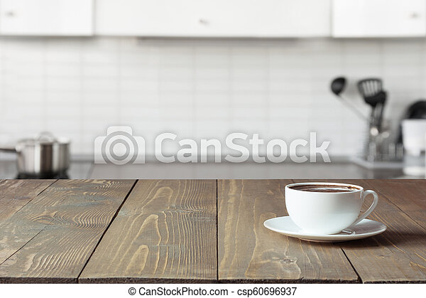 Cup of coffee on wooden board. Blurred kitchen as background. - csp60696937