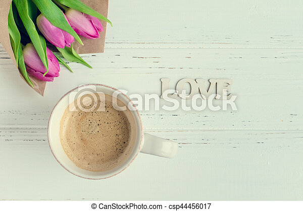Cup of coffee with bouquet of pink tulips and wooden word LOVE - csp44456017