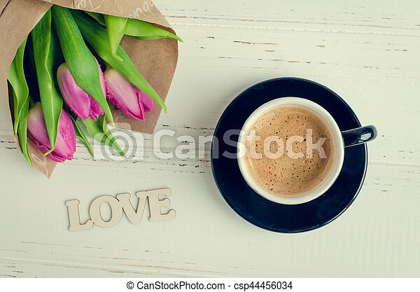 Cup of coffee with bouquet of pink tulips and wooden word LOVE - csp44456034
