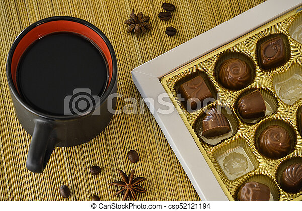 Cup of coffee with chocolate candies in a box - csp52121194