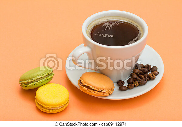 Cup of coffee with coffee beans and delicious macarons cakes of different color on peach background. - csp69112971
