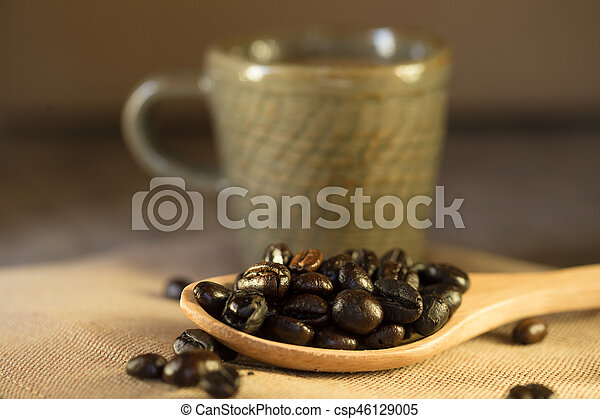 Cup of coffee with coffee beans on a beautiful brown background. - csp46129005