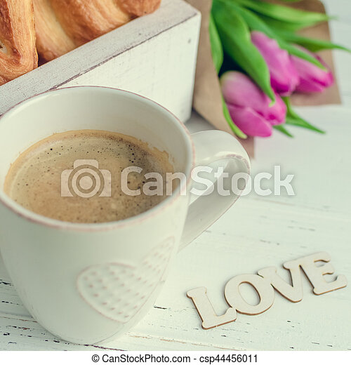 Cup of coffee with croissants, bouquet of pink tulips and wooden word LOVE - csp44456011