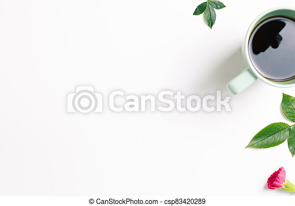 Cup of coffee with green leaves on white background. top view - csp83420289